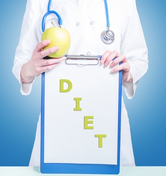 Clipboard with the words: Diet and Woman doctor with a green apple