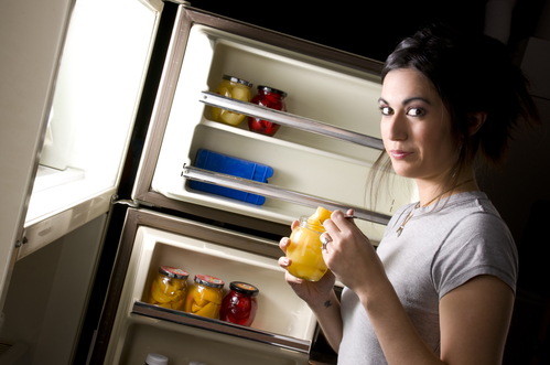 A sleepy woman lingers at the refrigerator door and gets suprised when you catch her nibbling outside her diet plan